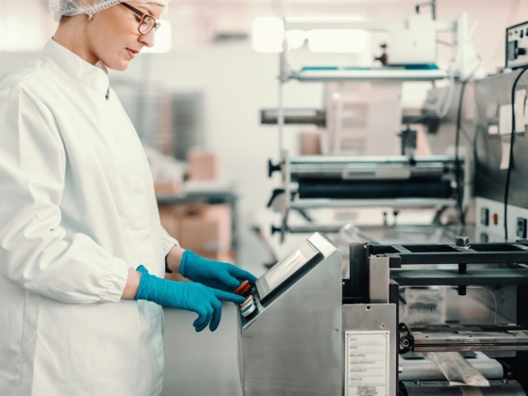 Young female employee in sterile uniform and blue rubber gloves turning on packing machine